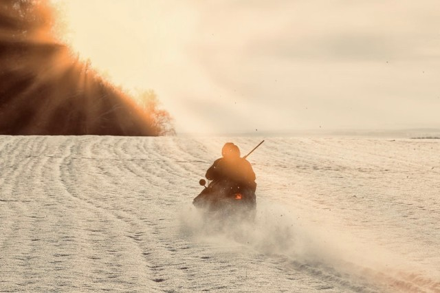 hunters by snowmobile in snowy field